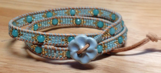 Blue wrap bracelet with ceramic flower button.
